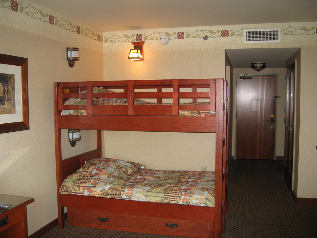 Orange polished bunk bed with solid wooden supports and lower storage drawer units for a flat in dubai.