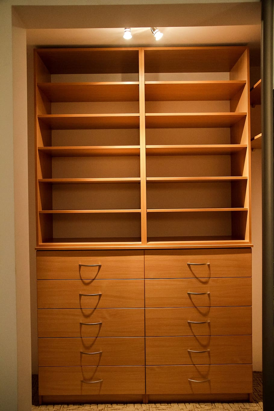 A simple armoire manufactured using hard maple consisting of shelves and drawer units underneath.