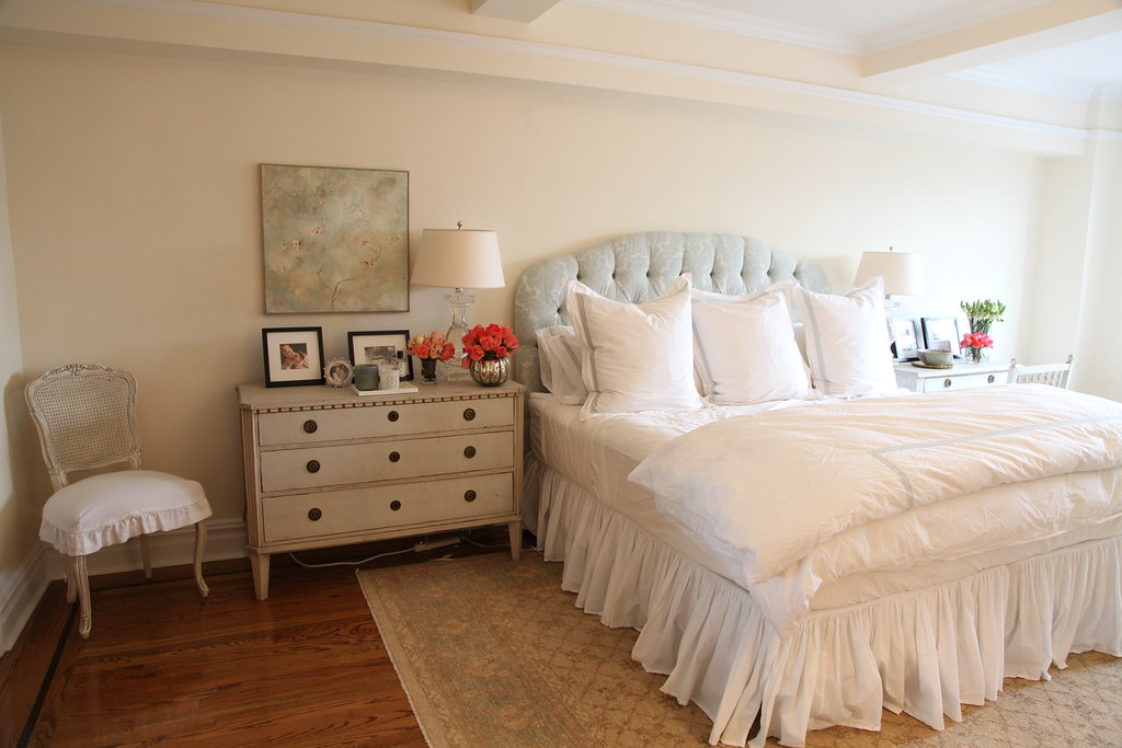Queen size upholstered bed accompanied by a huge bedside table consisting of multiple drawer units.