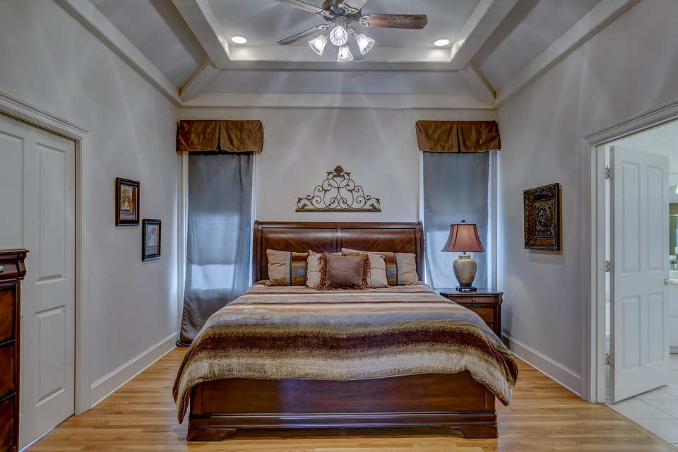 Lavishly designed huge master bed polished mahogany with bedside tables.