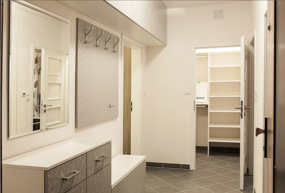 Storage area consisting of cabinetry installed with drawers and doors for the hallway along with wooden coat hangers and a hanging mirror. Best hallway furniture dubai.