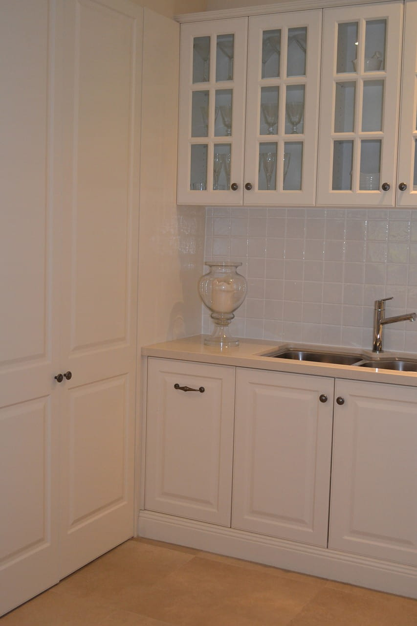 White painted kitchen cabinets with design doors, sink and faucet.