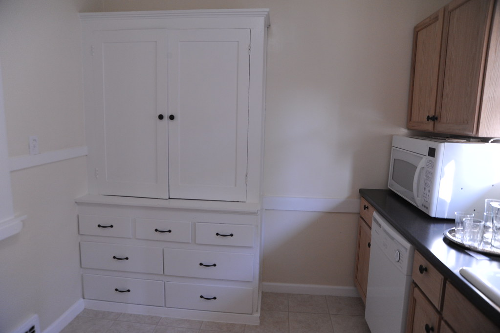 White painted decorative storage cabinet consisting of doors and drawer units.