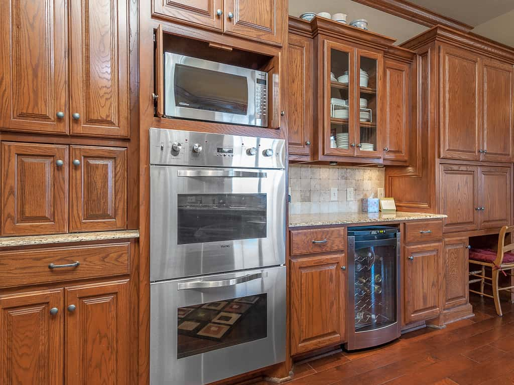 Mahogany veneer manufactured exquisite kitchen cabinets consisting of doors and drawer units with marble top.