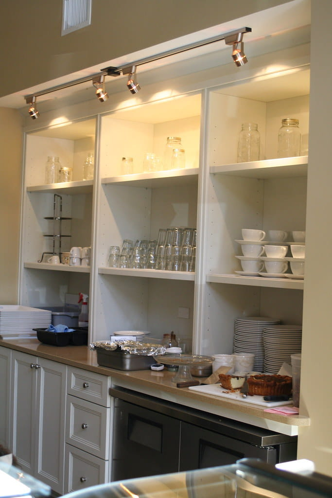 White painted decorative storage cabinet consisting of open shelving unit on top with lighting with lower part consisting of doors and drawers.