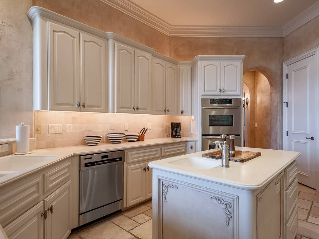 White painted design kitchen cabinetry consisting of doors and drawer units with white marble top along with that centre island topped with marble, sink and faucet.