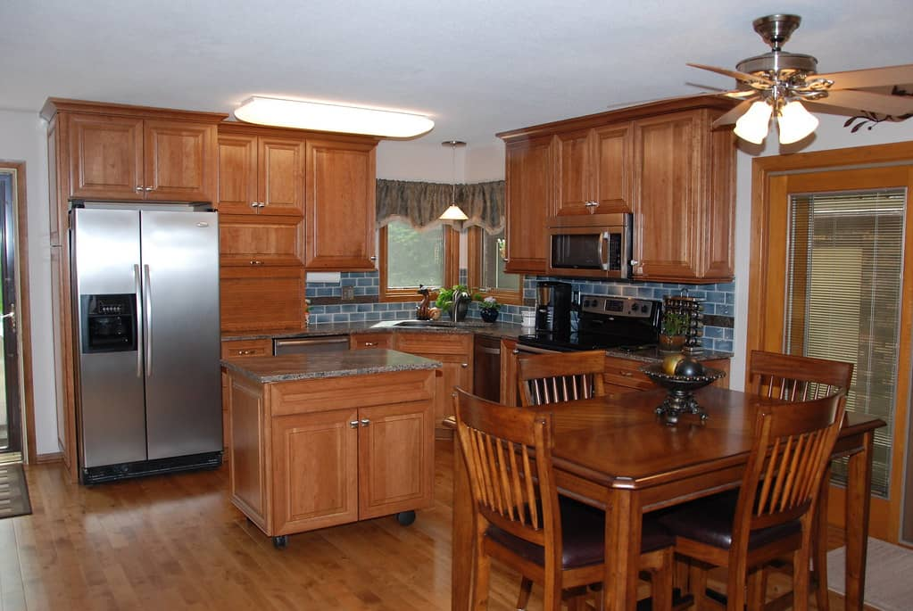 Cherry veneer manufactured kitchen upper and lower cabinets with marble top.