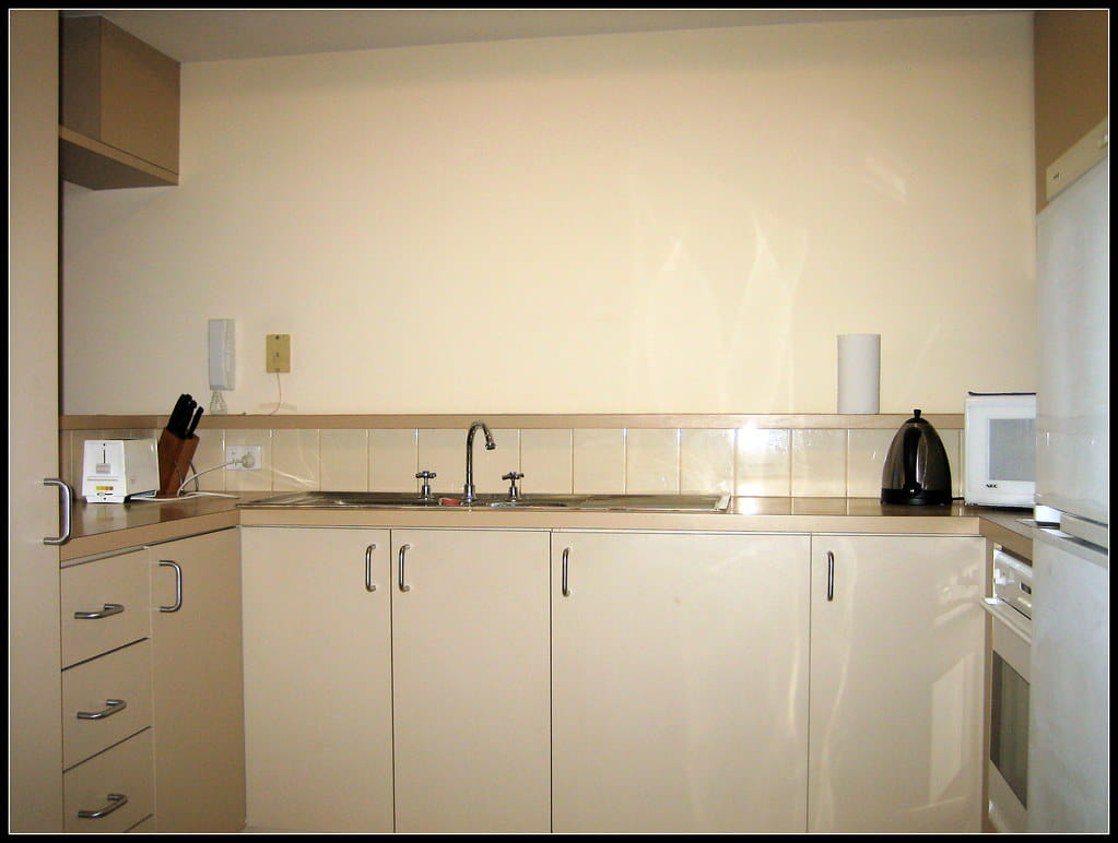 Off-white melamine manufactured L - Type kitchen cabinet with marble top, sink and faucet.