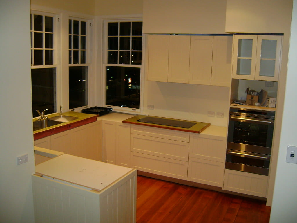 U - Type white painted kitchen lower and upper cabinets consisting of doors and drawer units.