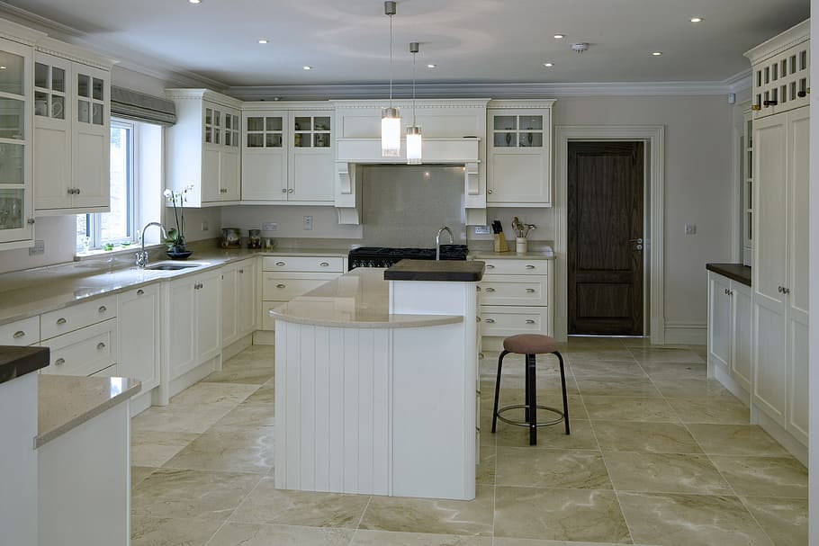 White painted kitchen cabinets along with two tier centre island topped with marble.