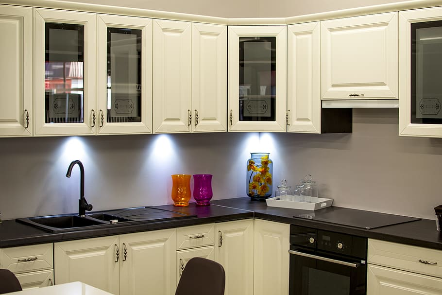 White painted kitchen cabinets with sand blasted glass within wooden door panels. The lower cabinets topped with black granite.