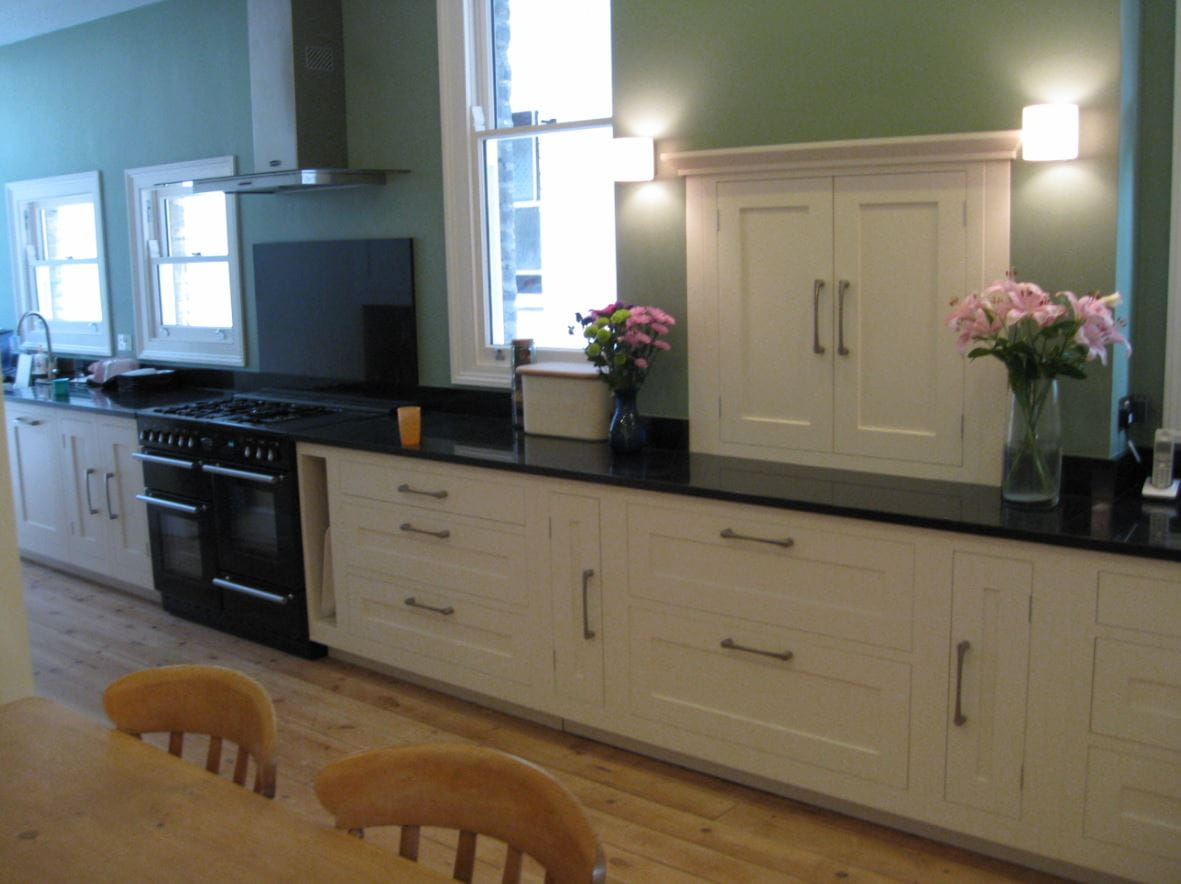 White painted kitchen cabinet with design doors and drawer units along with marble top.