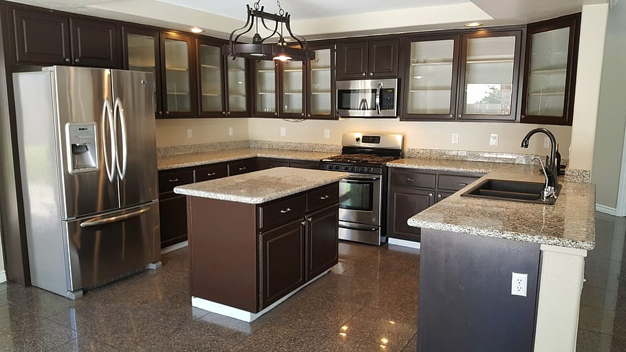 U - Type mahogany polished kitchen cabinets with glass panels for doors, lower cabinet topped with marble and centre island consisting of doors and drawer units for a villa in Dubai.