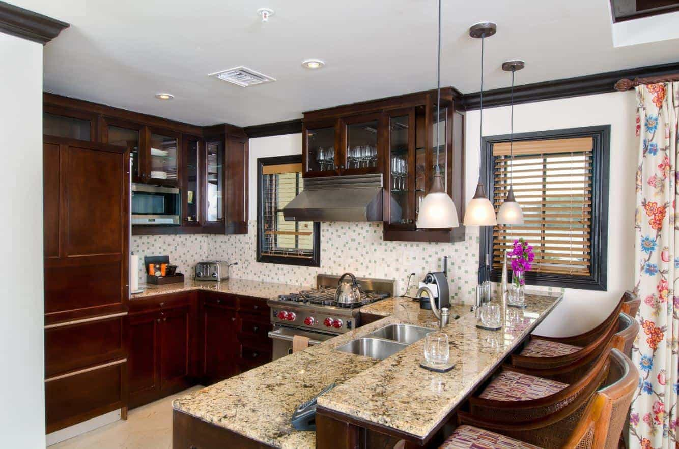Dark mahogany polished kitchen cabinets with marble top, sink and faucet along with adjoining dining table with space for bar chairs to slide in.