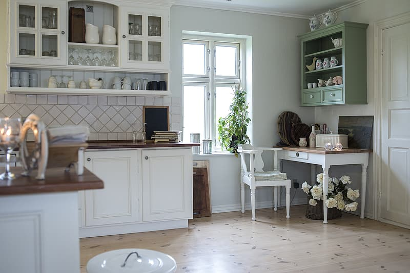 White painted decorative kitchen cabinetry consisting of solid wooden top and a light green painted open storage cabinet consisting of shelves within for a villa in Nad Al Hamar.