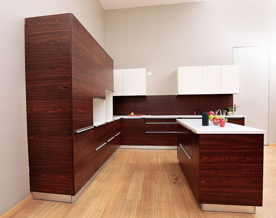 An abstract combination of rosewood and white kitchen cabinetry consisting of doors and drawer units along with centre island for a villa in Ras Al Khaimah. Best kitchen design Abu Dhabi.