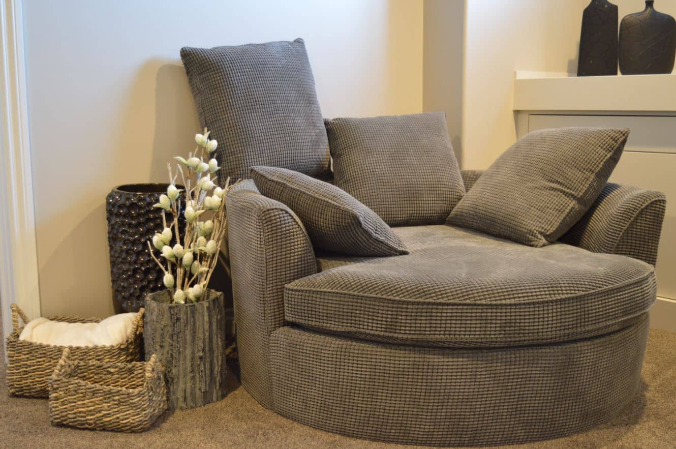 Round textured grey upholstered arm chair along with cushions.