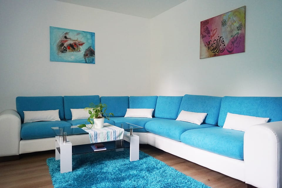 Light blue and white upholstered L - Type sofa along with centre table with glass top and melamine base.