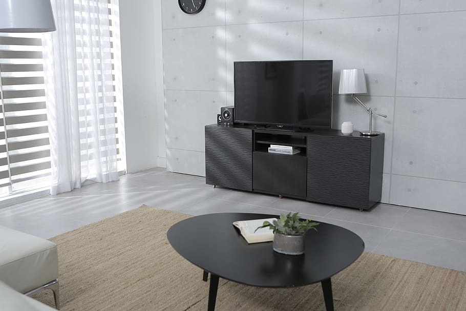 TV cabinet manufactured using blackish grey textured melamine MDF with doors on the outside and shelves and drawer units installed within. Similar coffee table was made abstract shaped with 3 legs underneath.