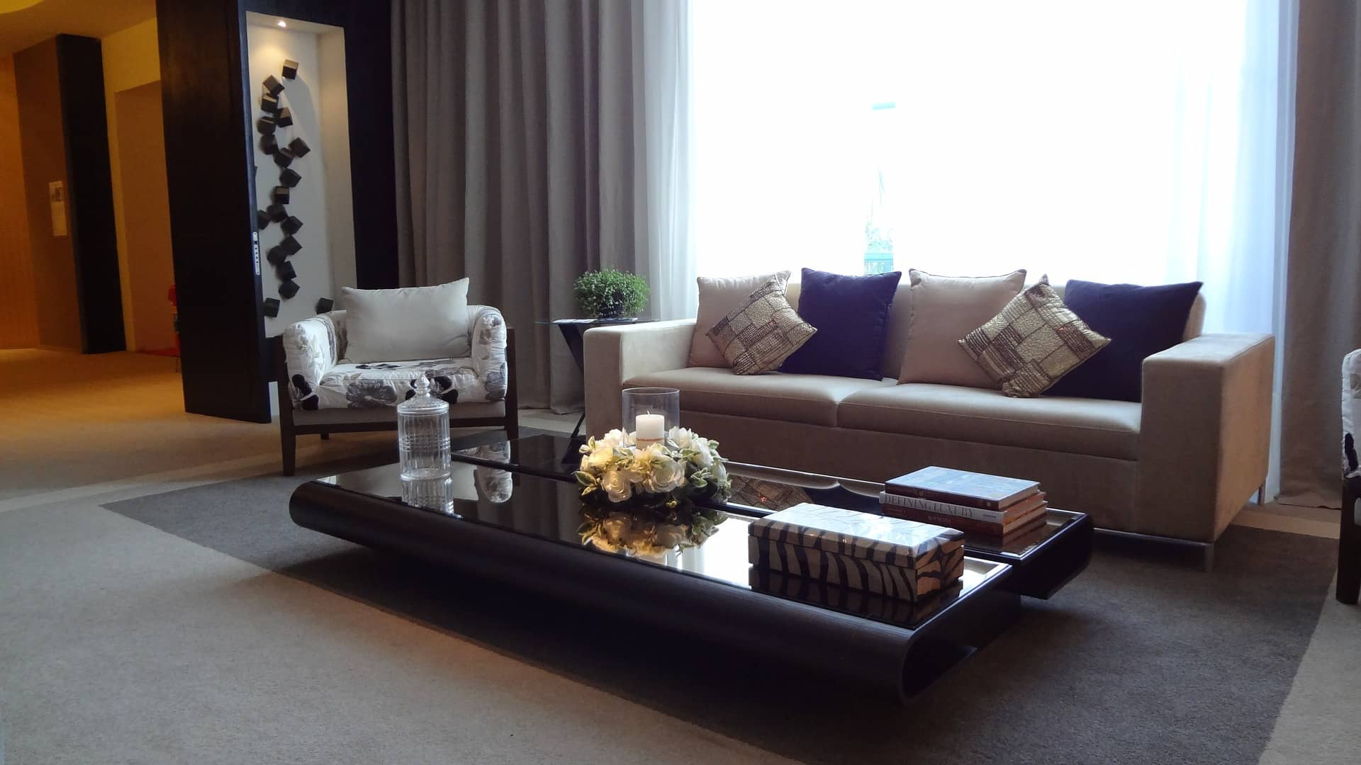 Beige upholstered 2 seater sofa along with contemporary designed two coffee tables painted black with glass top.