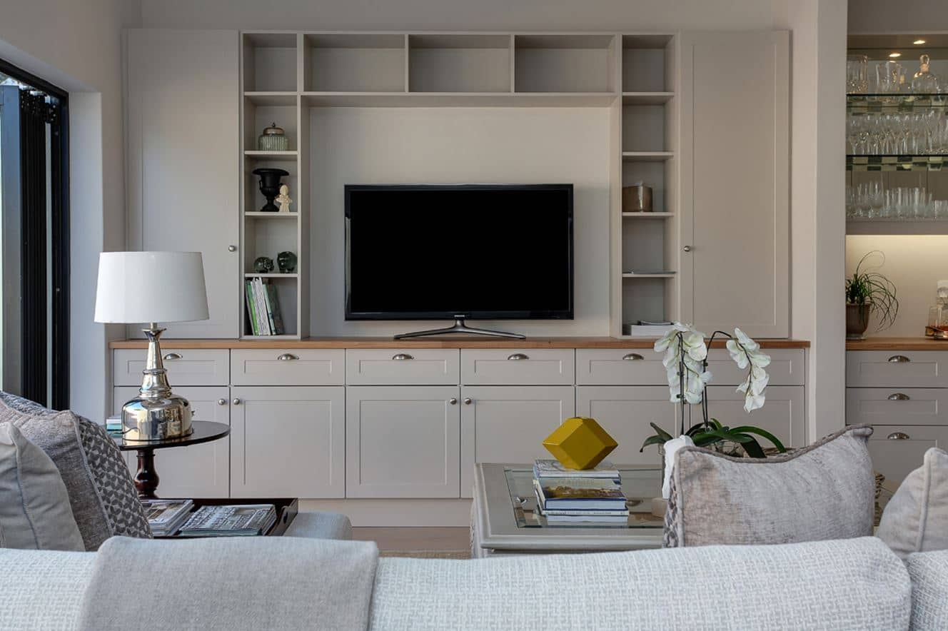 White painted TV cabinet with solid wooden top consisting of doors and shelves within along with decorative storage cabinetry on top consisting of shelving units for a villa in Ras Al Khaimah.