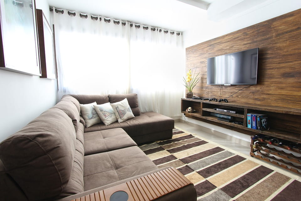 Walnut veneer manufactured TV unit consisting of shelves and bottle storage underneath along with upholstered L - Type futon.