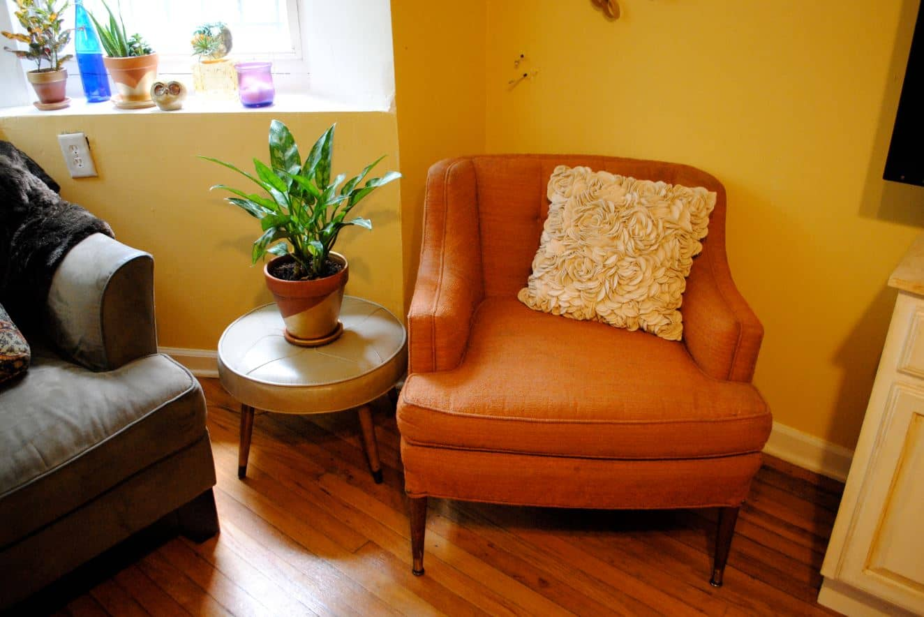 Orange upholstered arm chair with solid wooden legs.