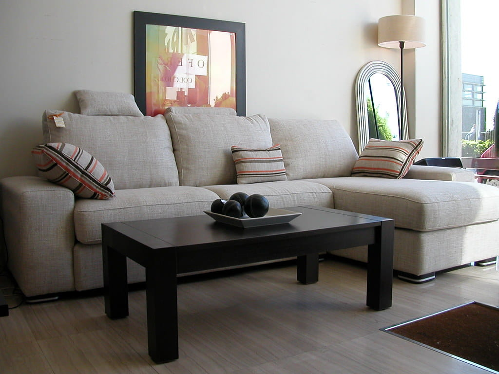 L - Type upholstered futon sofa along with black painted centre table manufactured using solid wood.