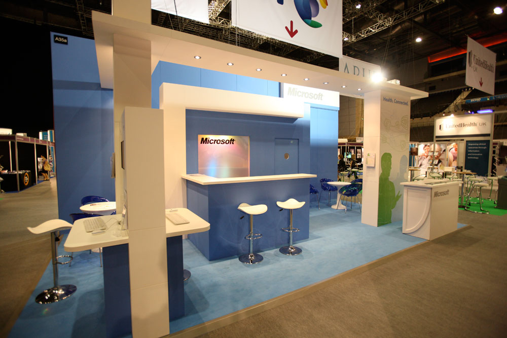 An exhibition stand made for microsoft at an exhibition hall, consisting of reception, counters, chairs, room partition and ceiling. Custom exhibition furniture dubai.