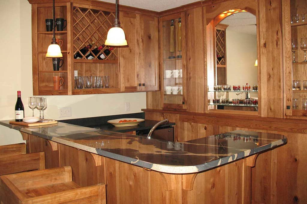 Wine room cabinetry manufactured using maple wood with centre table consisting of marble top and solid wooden stools.