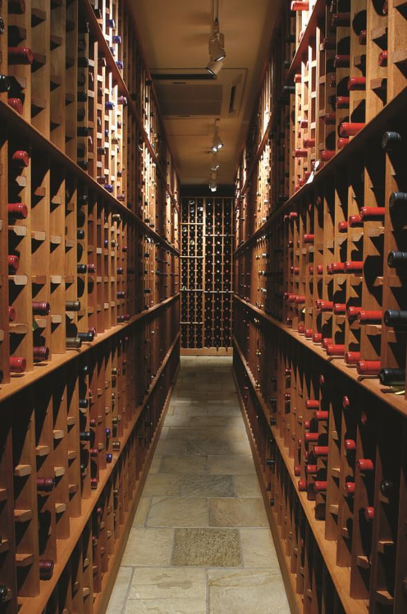 Storage unit for wine room consisting of open shelving units with partitions inside.