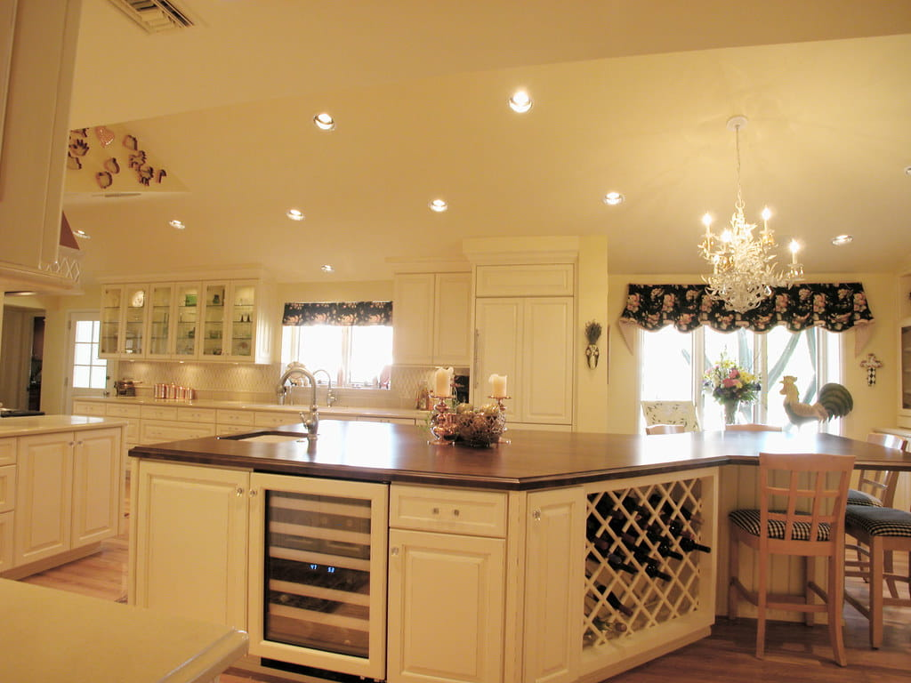 Wine room centre kitchen island consisting of sink and faucet with solid wooden top and lower storage area consisting of drawer units.
