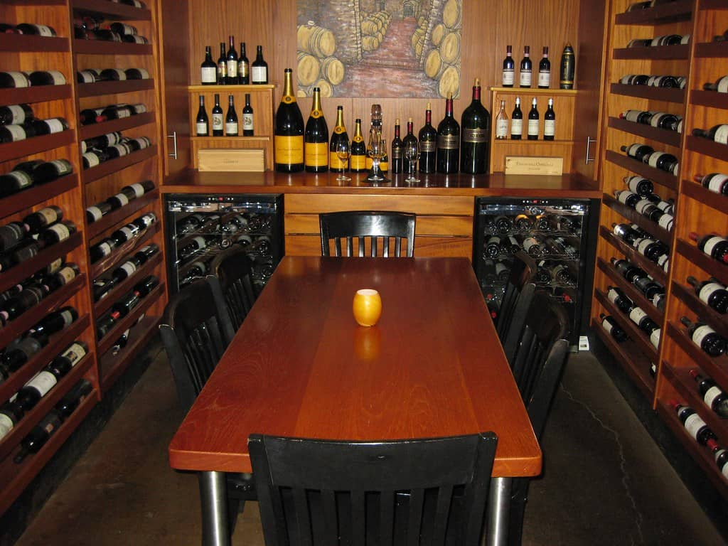 Wine room consisting of storage cabinet manufactured using mahogany solid wood with centre table manufactured from same solid mahogany wood and legs manufactured using metal legs.