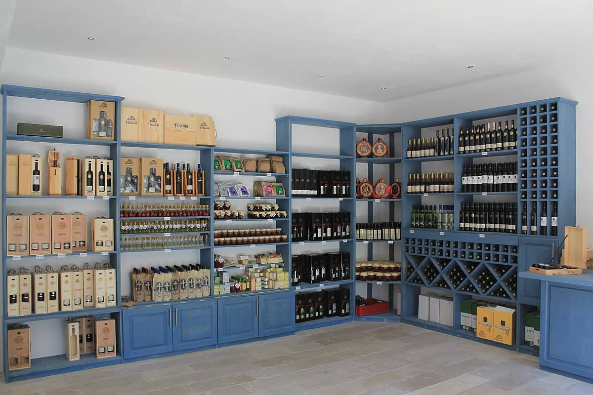 Navy blue painted wine storage cabinet consisting of open shelvings.