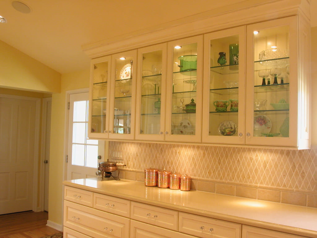 White painted floating cabinet with glass doors surrounded by wooden panel along with glass shelves inside.