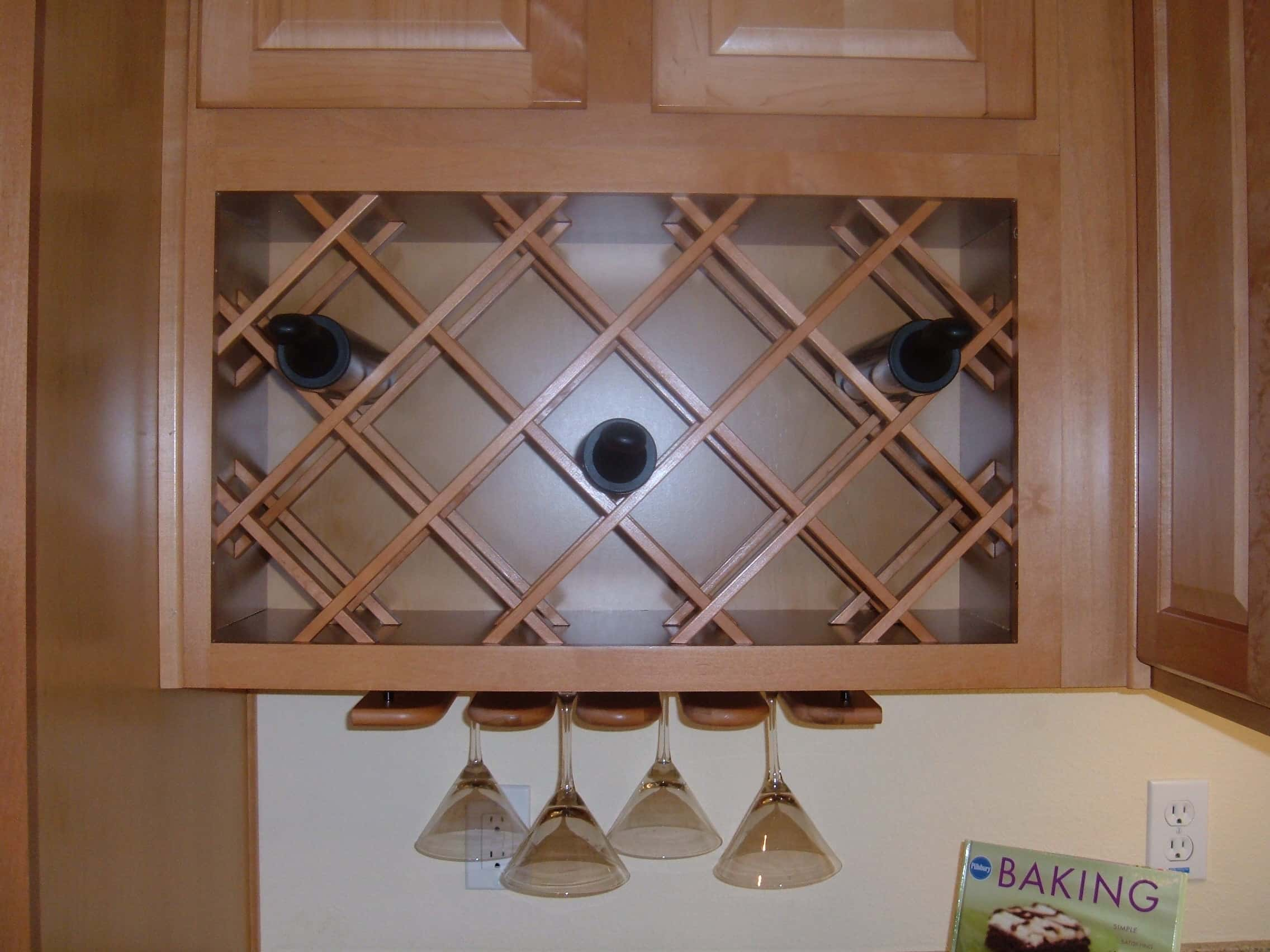 Wine storage area with cross angled shelves to lay down wine bottles along with lower hanging area for wine glass.