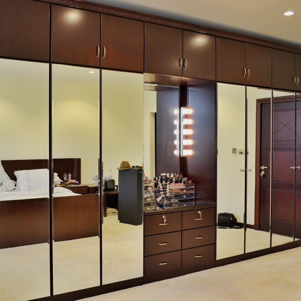 The whole width bedroom wardrobe was polished dark mahogany on the outside with golden handles, antique architraves and skirtings installed on the exterior.