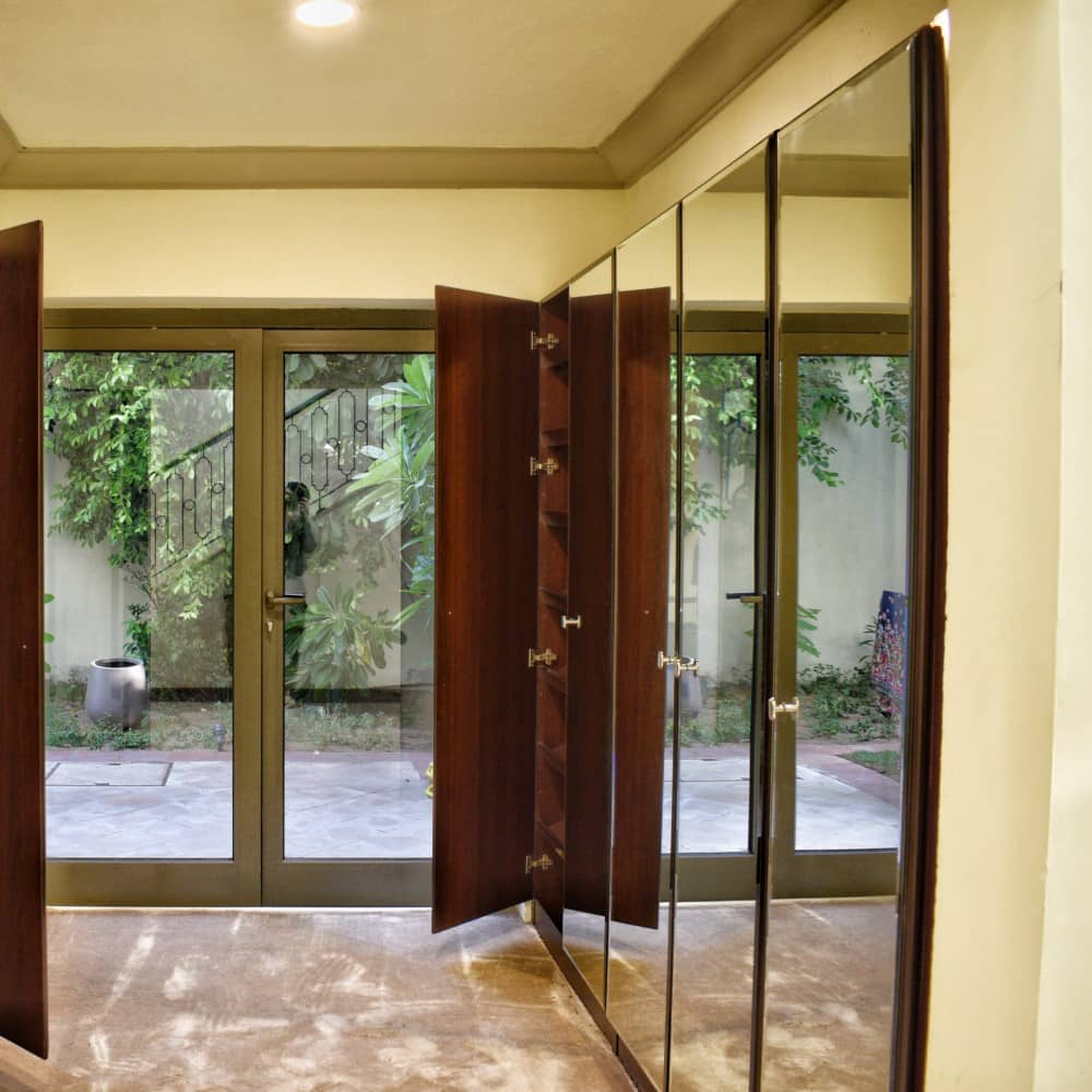 The exterior of the closet made for the hallway in Palm Jumeirah was polished using dark mahogany stain along with full mirror for doors.