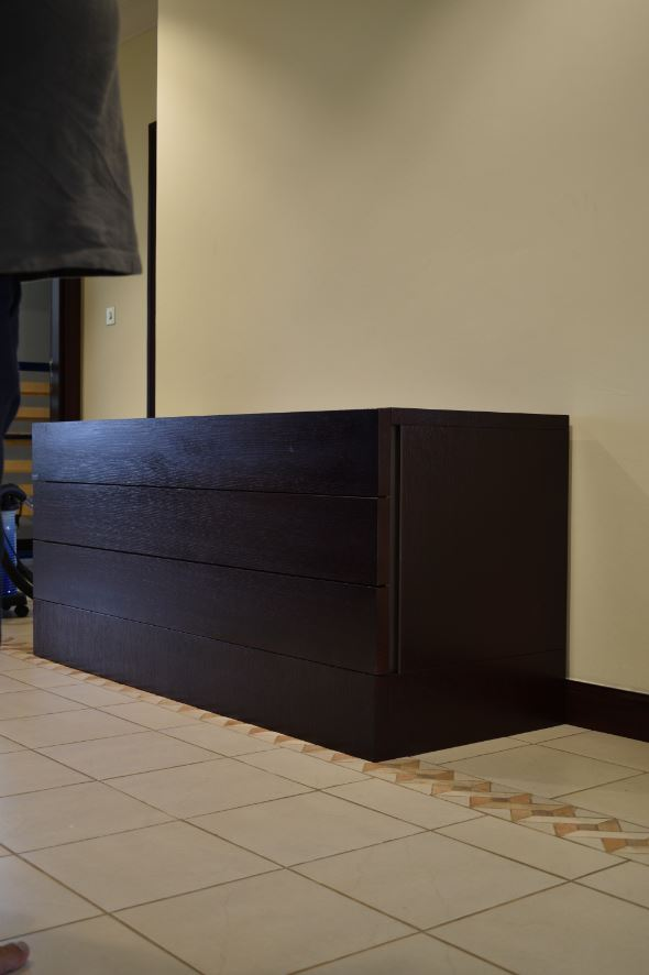 Manufacturing of a massive sideboard for a hall in palm jumeirah villa consisting of storage drawer units polished dark mahogany and installed with hettich soft closing railings.
