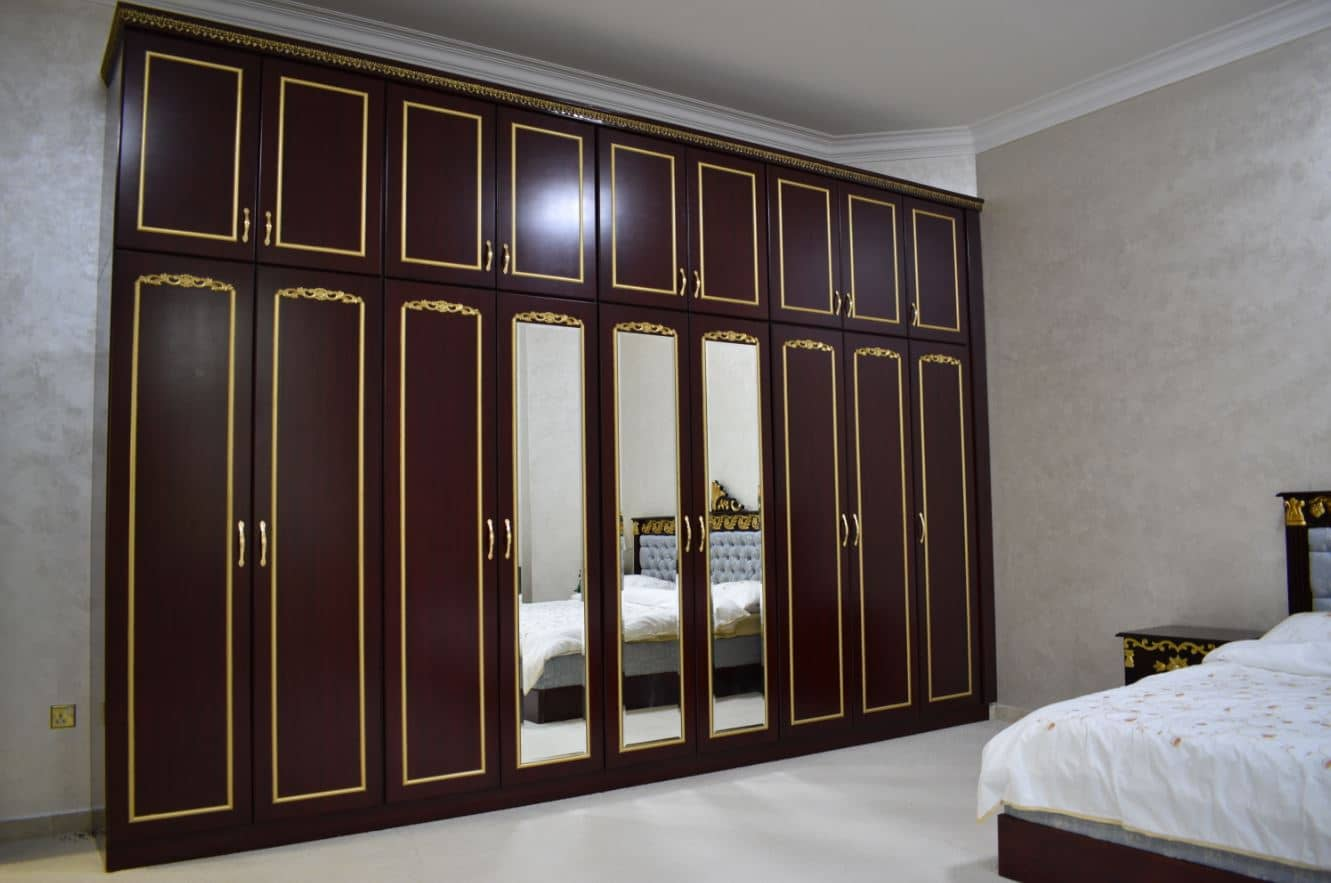 Another closet manufactured for 2nd bedroom located on ground floor manufactured using mahogany melamine with jet stain mahogany polishing on the outside with golden painted molding on top and mirrored doors.