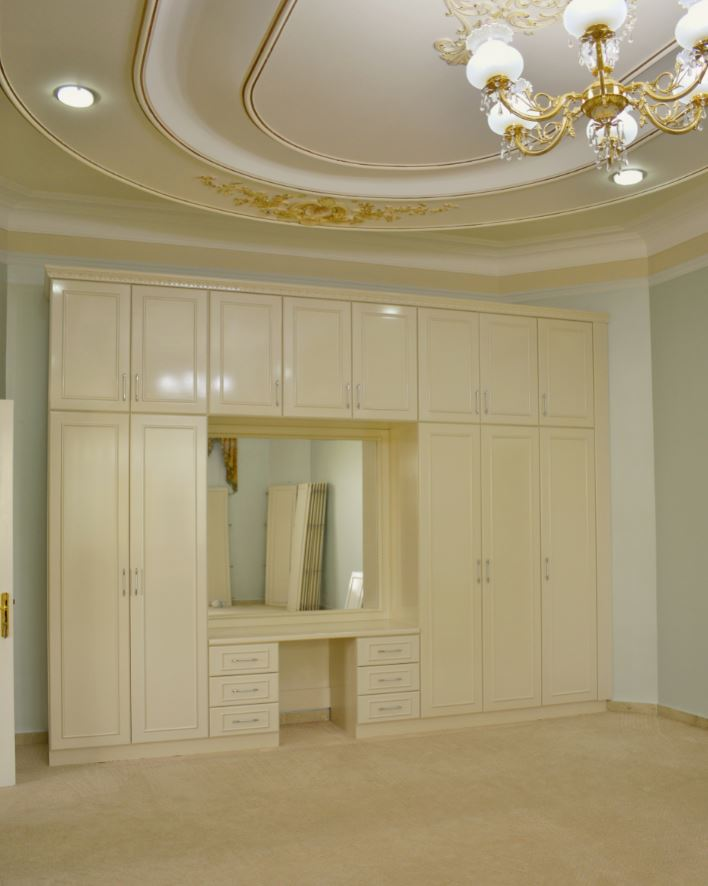 The wardrobe painted mother pearl was installed with a dressing table right in the middle consisting of mirror and drawer units. The mirror frame was installed with LED light strips.