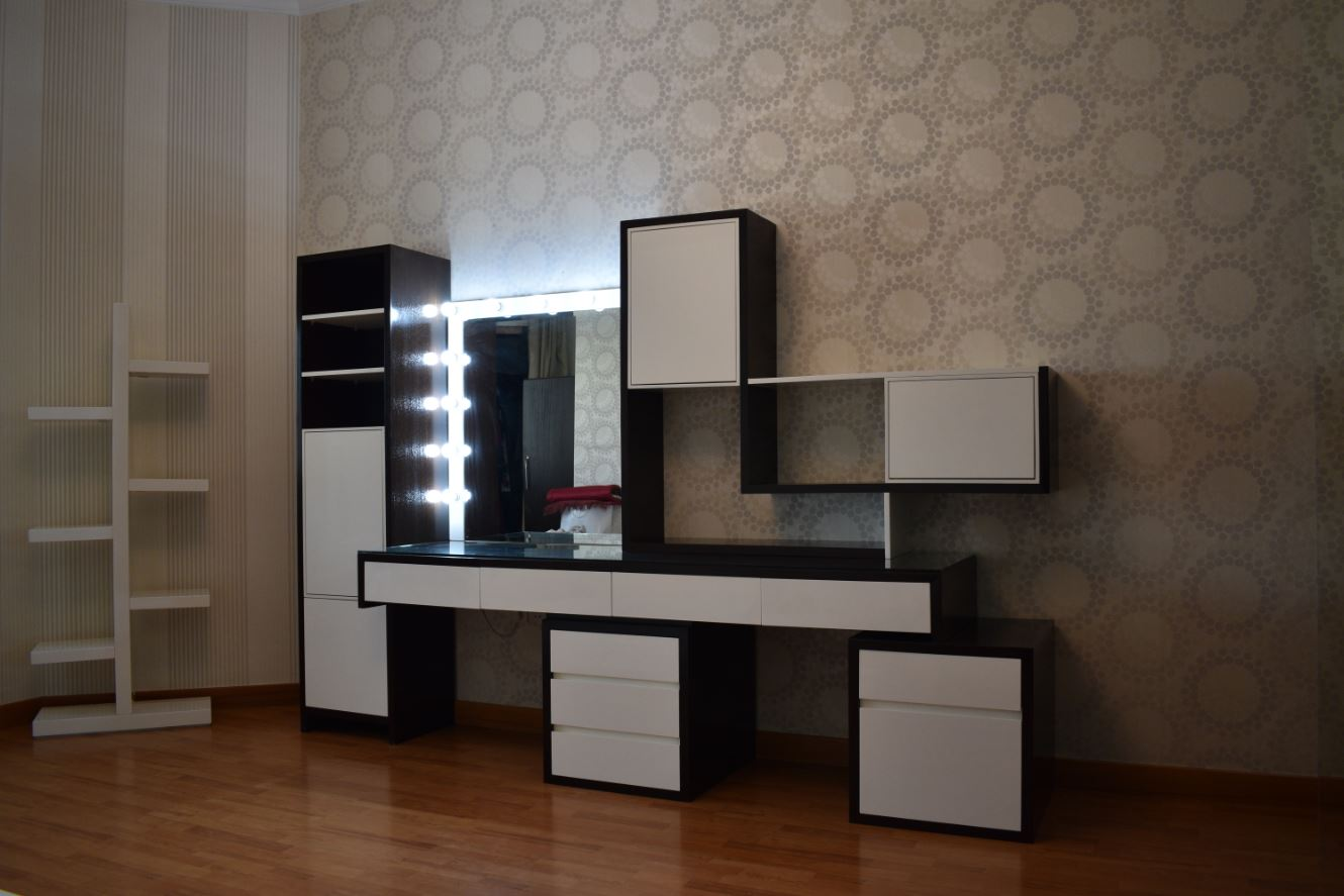 The dressing table made with abstract colors and designs. The dressing table was painted white and polished dark mahogany consisting of bevelled mirror and oddly placed shelves and storage areas for a residence in dubai.