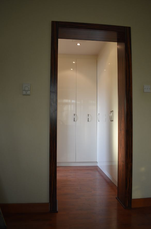 L-Type glossy white painted wardrobe consisting of shelves and hangers with huge doors for a house in dubai. Best carpentry dubai.