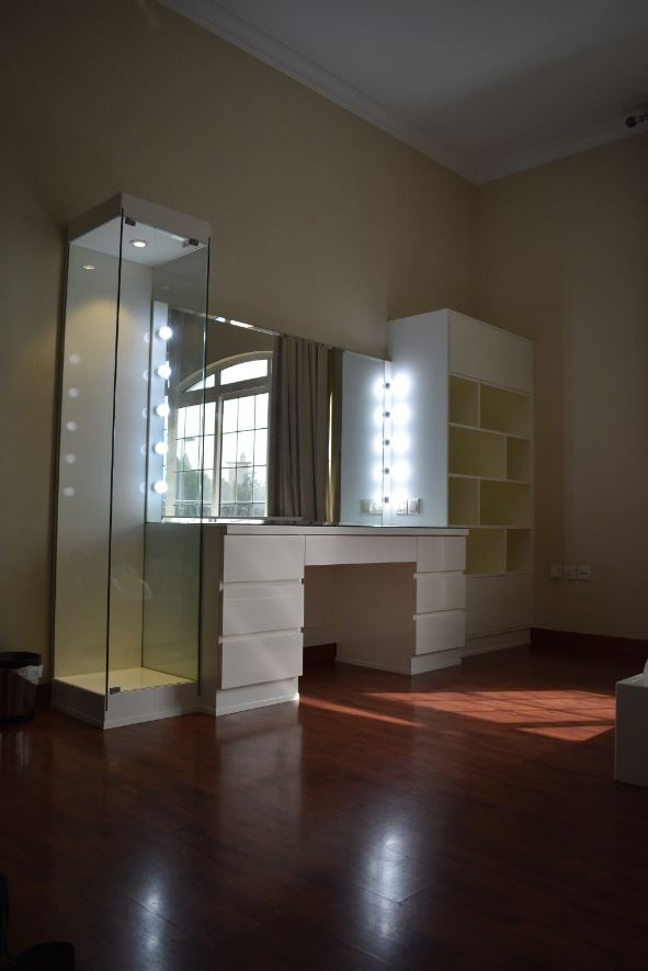 Dressing table made consisting of centre dresser with bevelled mirror with surround LED light bulbs, a bookcase and planter surrounded by glass coverings.