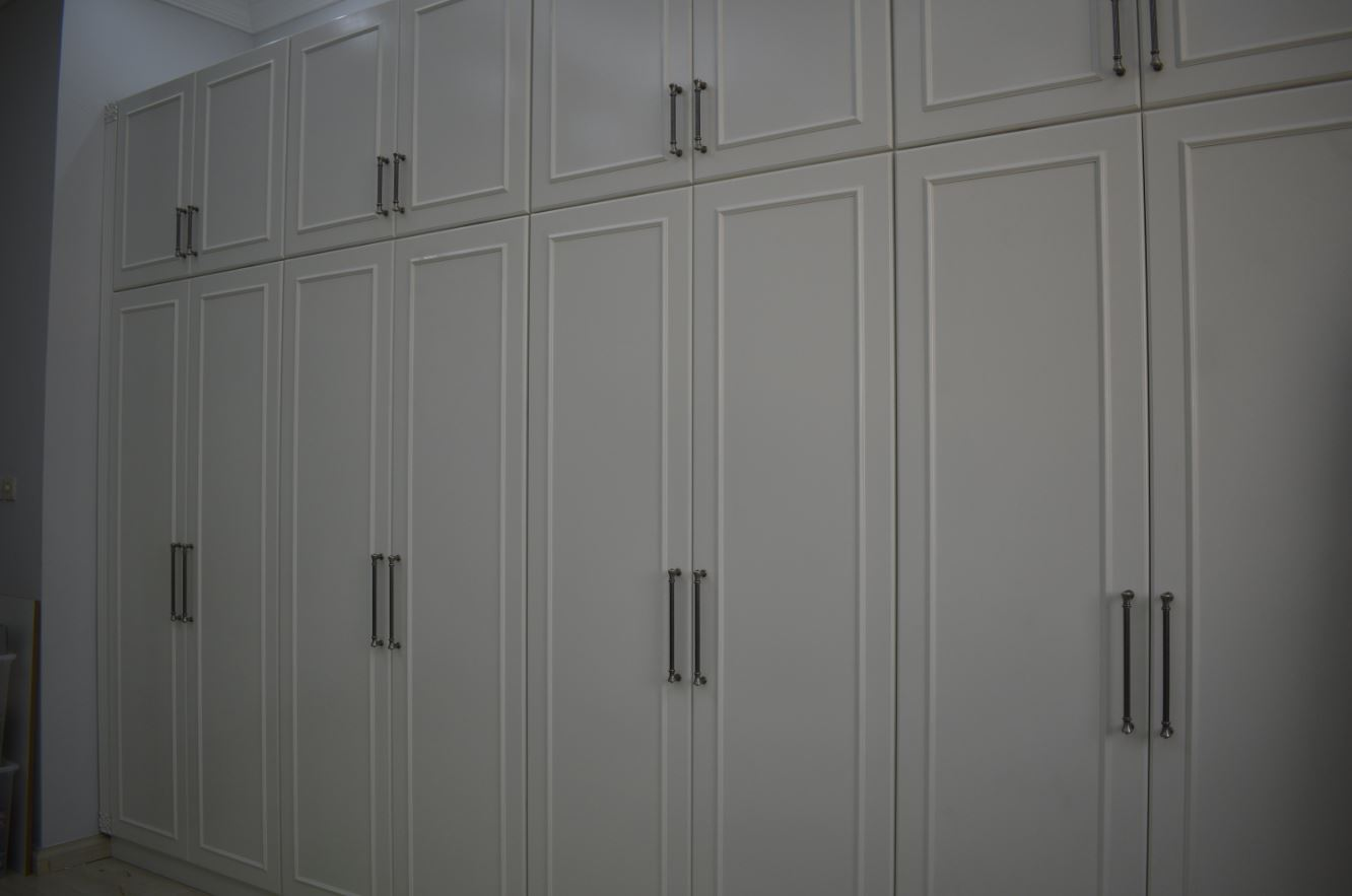 Full view of the closet manufactured for house in nad al hamar consisting of hangers, pull out shelves and drawer units.