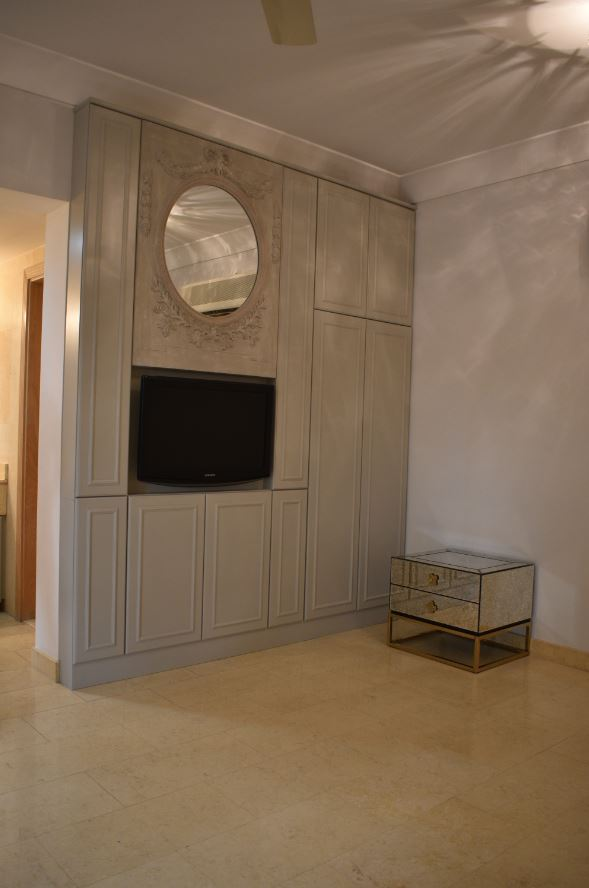 Full view of the tv cabinet manufactured using MDF with one side white melamine and the exterior part painted matte grey for villa in mirdif, dubai.