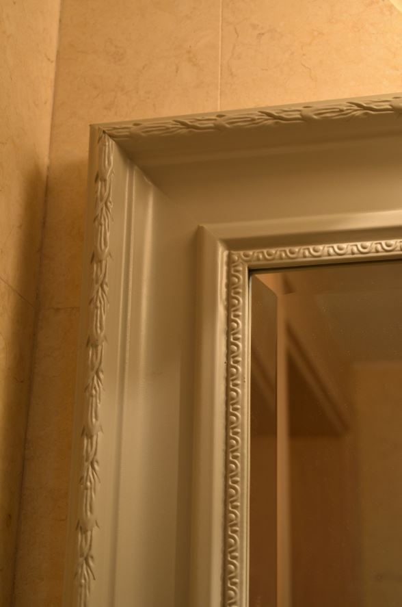 Close view of the bathroom mirror frame showcasing the artistic design that it was finished with.