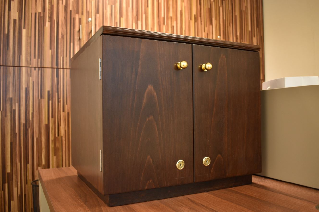 Closed view of the ash veneer artistic design box depicting the beautiful grains of ash veneer with doors installed with golden coated knobs for an office in dubai.