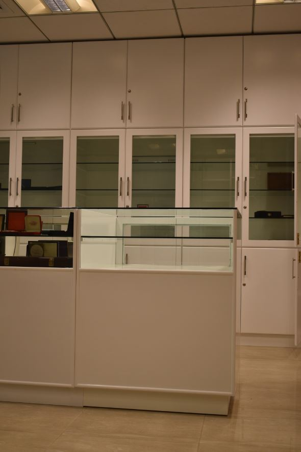 High end full width storage office cabinets consisting of glass doors in the middle and smaller doors at the upper and lower sides to hide away mess for an office in dubai.