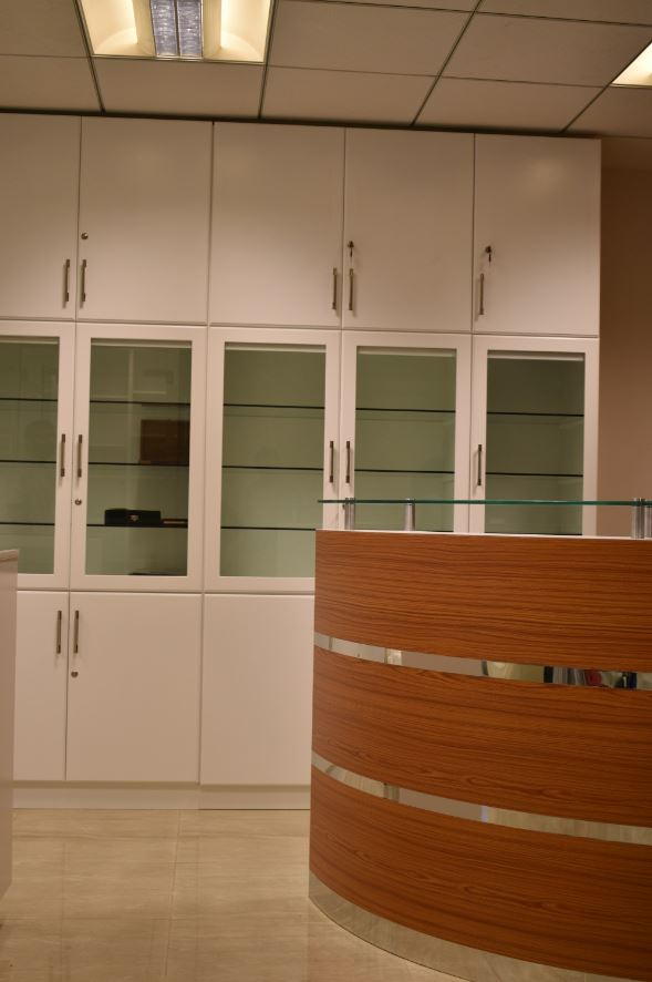 Close view of the tempered 6 MM glass installed within wooden frame doors for cabinets in dubai office.